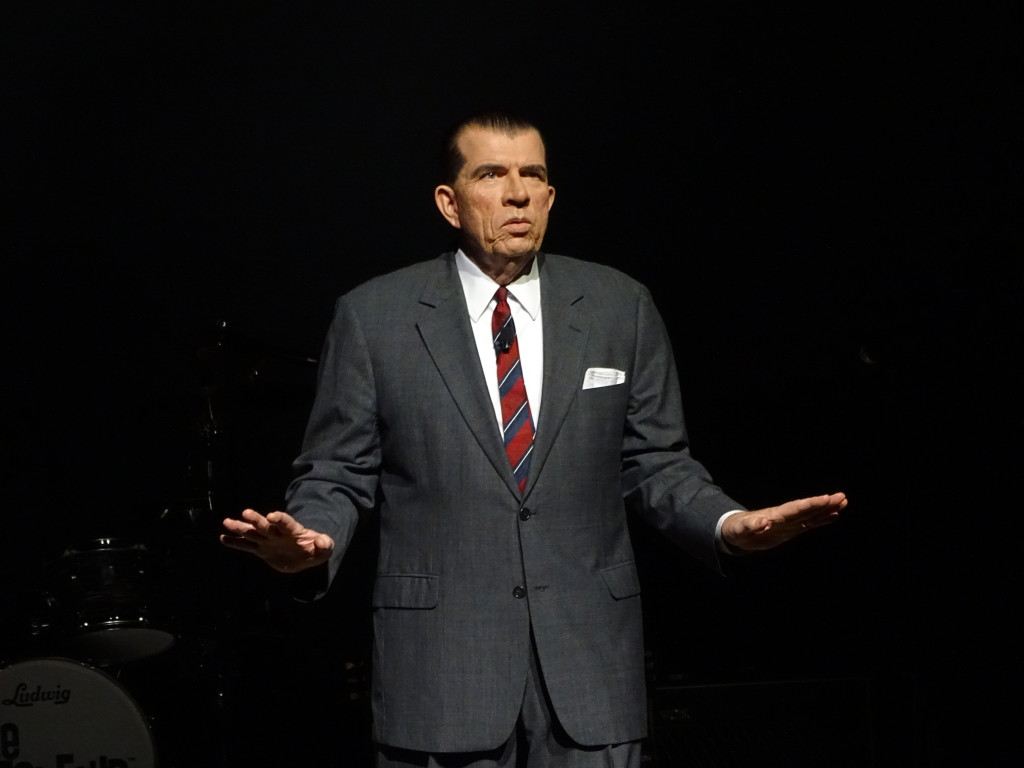 """""""Ed Sullivan,"""" played by George Trullinger, introduces the band."""